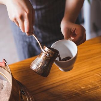 Mano femenina que vierte el café turco en la taza de cerámica blanca en el restaurante