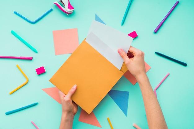 Mano femenina quitando la tarjeta del sobre sobre los accesorios de papelería