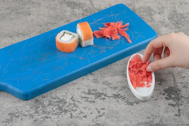 Mano femenina recogiendo jengibre encurtido de la tabla de cortar azul