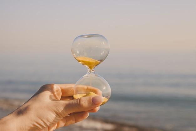 Mano femenina con un reloj de arena contra la playa de arena de un país caluroso, el tiempo corre entre los dedos, el concepto se remonta al pasado