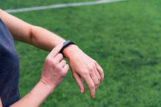 Mano femenina con reloj inteligente sobre fondo verde del estadio de deportes al aire libre