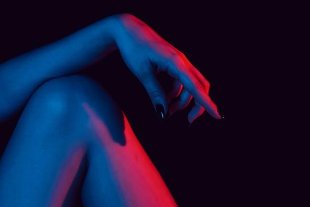 Mano femenina en la rodilla de cerca con luz de neón