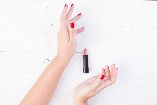 Mano femenina con uñas rojas tomando lápiz labial