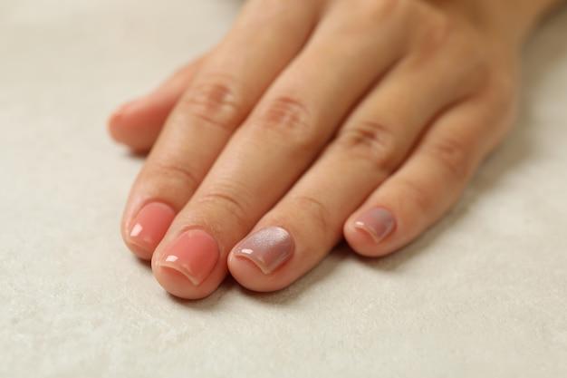 Mano femenina con uñas rosadas