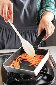 Mano femenina saltear zanahorias en una sartén, proceso de cocción casera en la cocina para hacer kimbap / gimbap coreanos