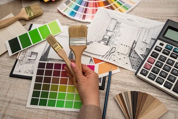 Mano femenina selecciona un color de la paleta en el plan arquitectónico, concepto de renovación