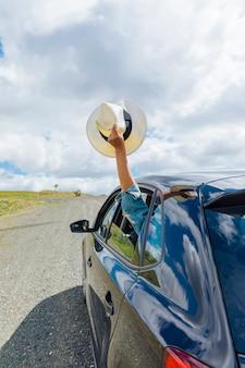 Mano femenina con sombrero fuera de la ventana del coche
