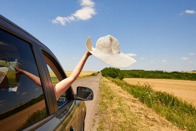 Mano femenina con un sombrero desde la ventanilla de un coche en la carretera.