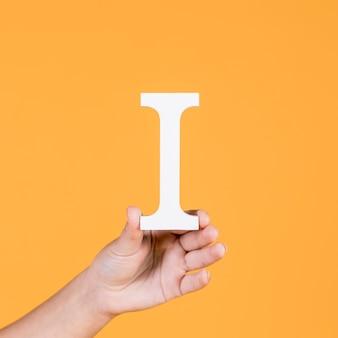 Mano femenina sosteniendo el alfabeto capital i