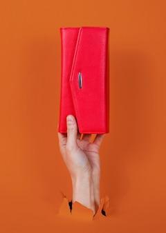 Mano femenina sosteniendo una billetera roja a través de papel naranja rasgado. concepto de moda creativa minimalista