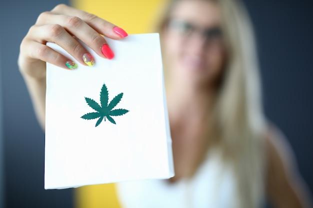 Mano femenina sosteniendo una bolsa de papel con marihuana