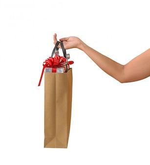 Mano femenina sosteniendo bolsas de papaer marrón en blanco llenas de cajas de regalo adornadas
