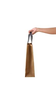 Mano femenina sosteniendo bolsas de papaer marrón en blanco