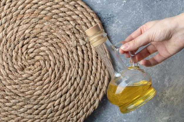 Mano femenina sosteniendo una botella de aceite.