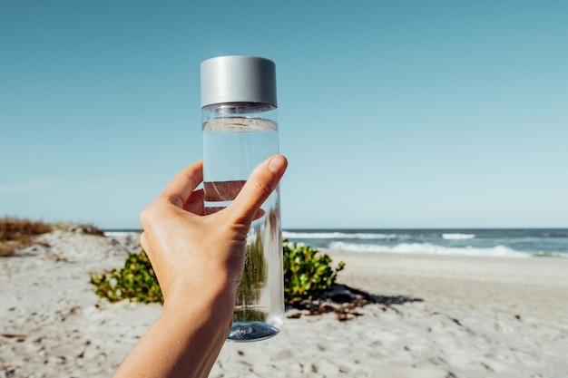 Mano femenina sosteniendo una botella de agua potable al aire libre en la orilla del mar concepto de salud para el equilibrio del agua contenedor de agua reciclable h2o
