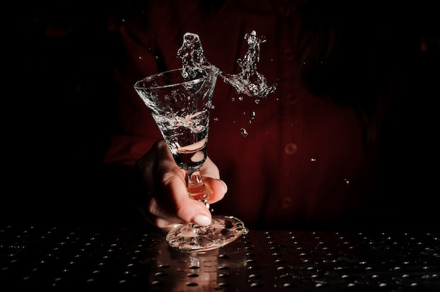 Mano femenina sosteniendo una copa de cóctel llena de una bebida fresca