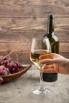 Mano femenina sosteniendo una copa de vino blanco sobre la mesa de mármol.