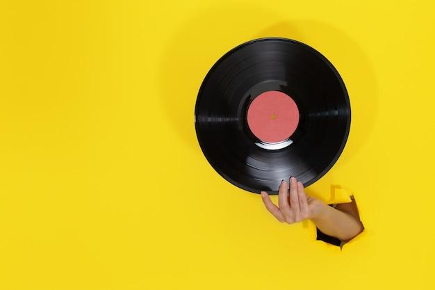 Mano femenina sosteniendo un disco de vinilo a través del agujero rasgado en la pared de papel amarillo. concepto retro minimalista