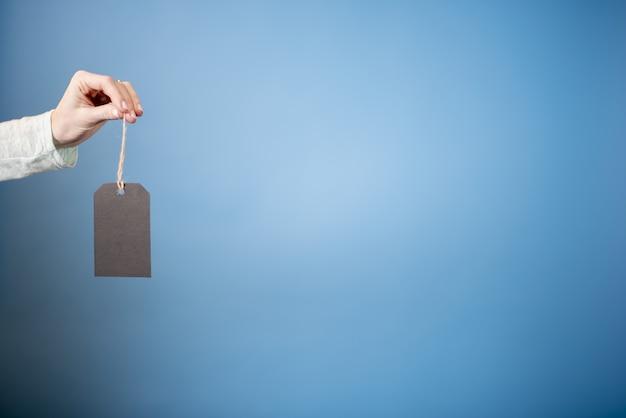 Mano femenina sosteniendo una etiqueta en blanco con una pared borrosa