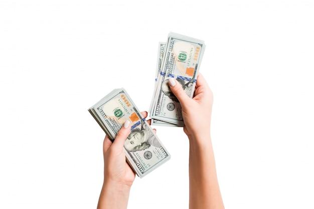 Mano femenina sosteniendo un fajo de billetes de un dólar
