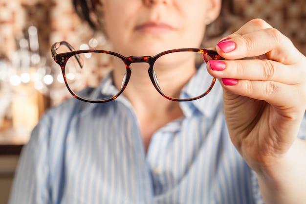 Mano femenina sosteniendo unas gafas con montura marrón