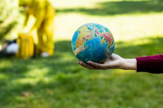 Mano femenina sosteniendo globo con parche médico. parque verde borroso en el fondo