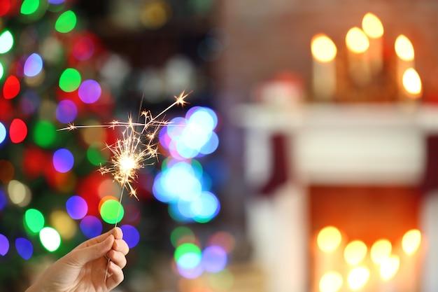 Mano femenina sosteniendo hermosa bengala en navidad en casa