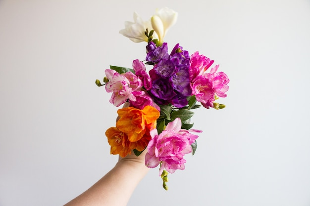 Mano femenina sosteniendo un hermoso ramo de flores de colores