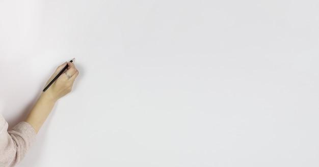 Mano femenina sosteniendo un lápiz sobre fondo blanco, escribe a lápiz sobre una pared gris, copie el espacio.