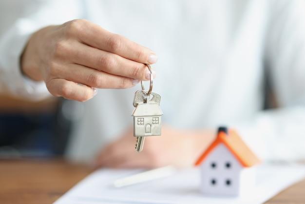 Mano femenina sosteniendo llaves con llavero cerca de la casa de juguete closeup