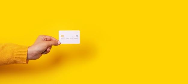 Mano femenina sosteniendo maqueta de tarjeta de crédito blanca en blanco, tarjeta con chip electrónico sobre fondo amarillo