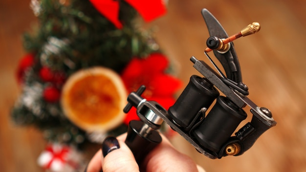 Mano femenina sosteniendo la máquina de tatuaje negro sobre fondo borroso árbol de navidad