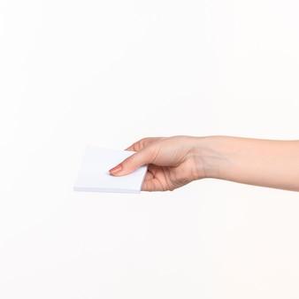 Mano femenina sosteniendo papel en blanco para registros sobre fondo blanco con la sombra derecha