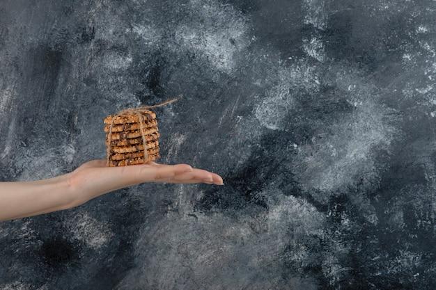 Mano femenina sosteniendo la pila de galletas de avena sobre fondo de mármol.