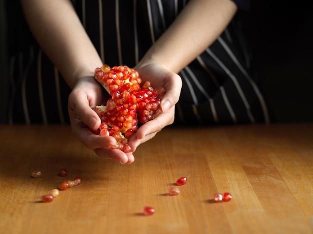 Mano femenina sosteniendo semillas de granada en la mesa de la cocina de madera