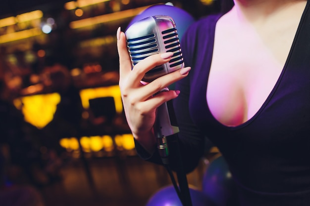 Mano femenina sosteniendo un solo micrófono retro