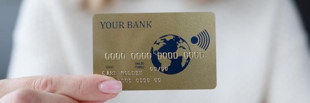 Mano femenina sosteniendo la tarjeta bancaria de crédito closeup
