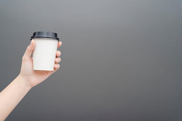 Mano femenina sosteniendo una taza de papel café en gris