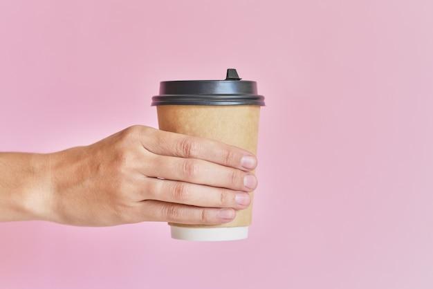 Mano femenina sosteniendo la taza de papel para café para llevar sobre fondo rosa