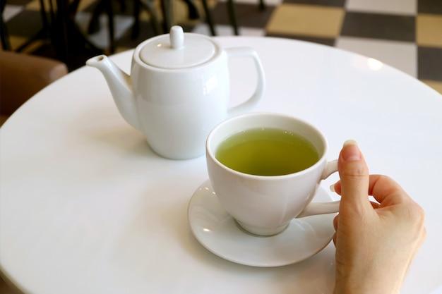 Mano femenina sosteniendo una taza de té verde en una mesa redonda blanca con tetera en segundo plano.