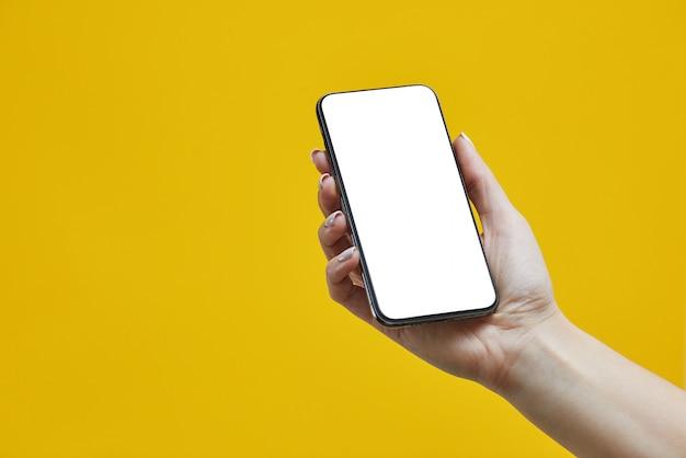 Mano femenina sosteniendo teléfono celular negro con pantalla en blanco sobre amarillo