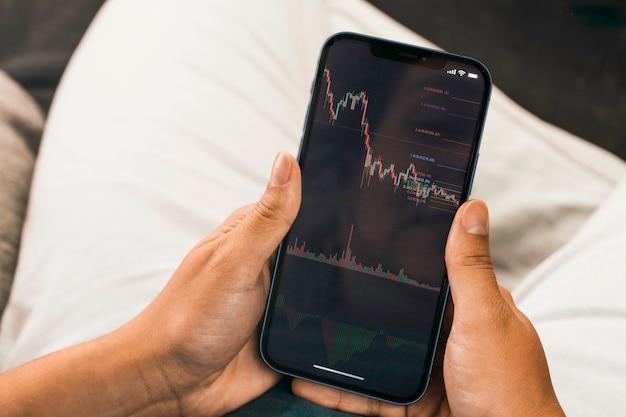 Mano femenina sosteniendo un teléfono inteligente con gráfico de mercado de valores financieros en la pantalla. bolsa. río de janeiro, rj, brasil. septiembre de 2021.