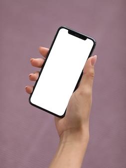 Mano femenina sosteniendo un teléfono inteligente con pantalla en blanco