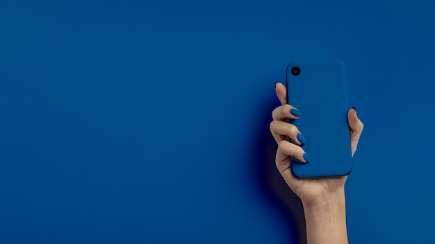 Mano femenina sosteniendo teléfono móvil sobre fondo de color pantone