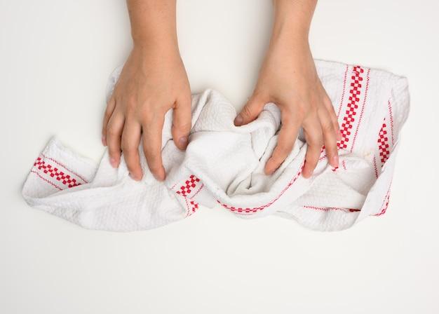 Mano femenina sosteniendo una toalla de cocina blanca sobre una mesa blanca, vista superior