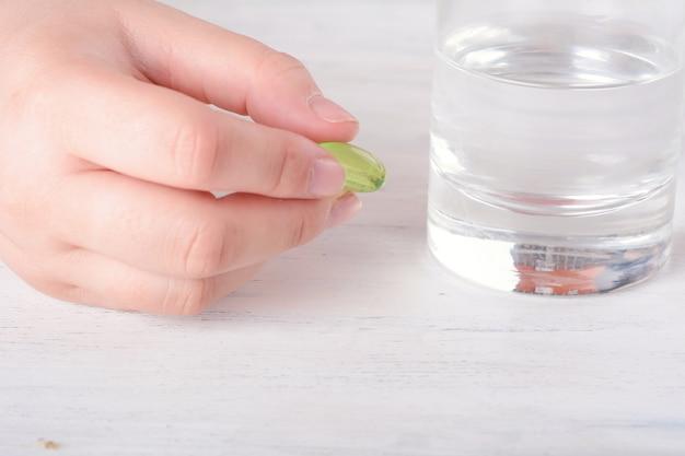 Mano femenina sosteniendo una pastilla.
