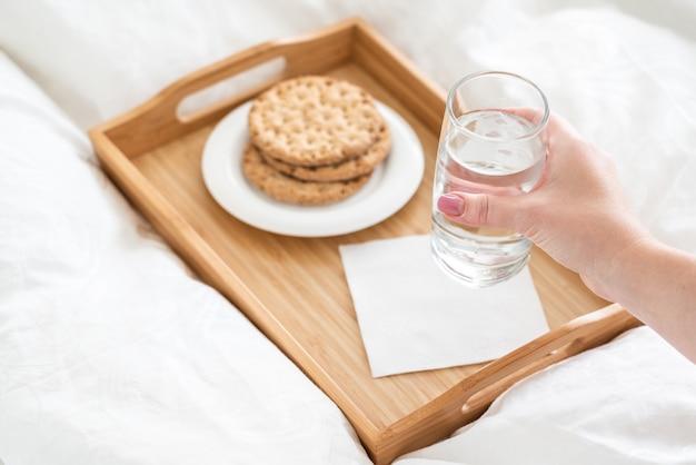 Mano femenina sosteniendo un vaso de agua sobre la bandeja con galletas en la cama