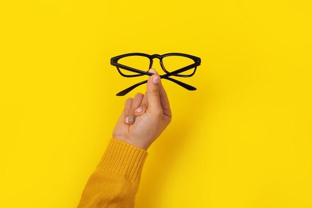 Mano femenina sosteniendo vasos sobre amarillo