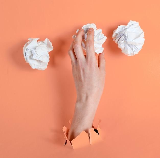 Mano femenina sostiene bolas de papel arrugadas a través de papel amarillo rasgado. concepto de negocio de idea minimalista