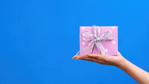 Mano femenina sostiene una caja de regalo